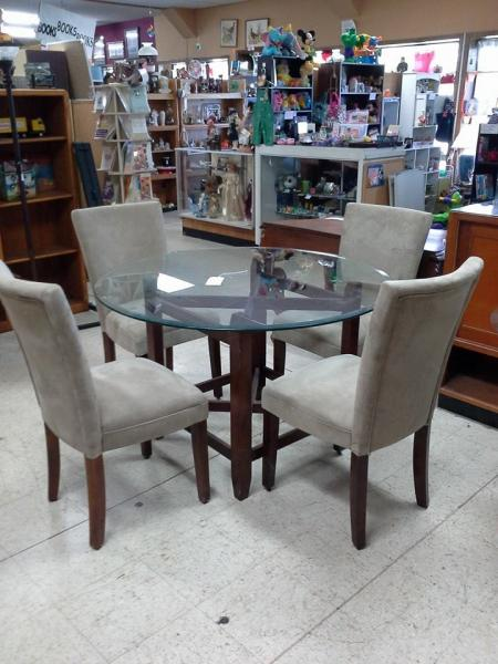 This glass table with grey suede, high back chairs would make a great addition to any dinning room!